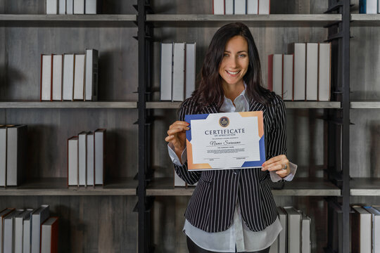 caucasian business woman posing with certificate of appreciation recieved from business performace competition
