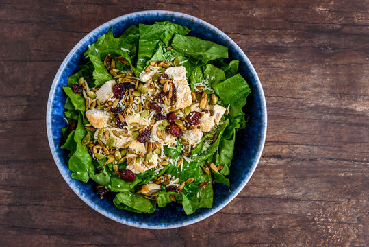 Healthy meal, blue food bowl with romaine lettuce, grille chicken breast, parmesan cheese, and salad topper of roasted nuts and seeds