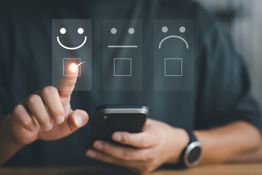 Customer service evaluation concept. Businessman pressing face smile emoticon show on virtual screen at smartphone.