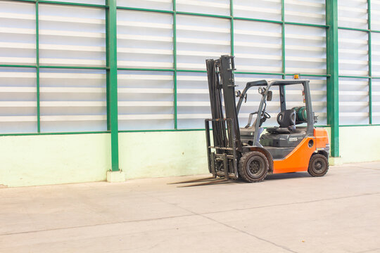 The 2.5 ton forklifts inside empty warehouse with wall background