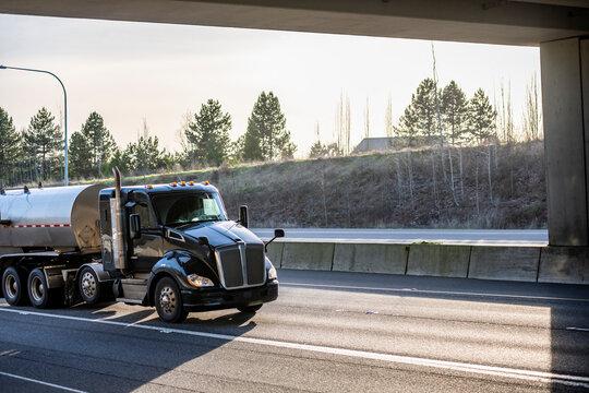 Stylish black day cab big rig semi truck transporting fuel in tank semi trailer running on the sunny road under the bridge