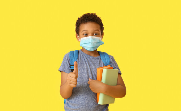 Little African-American schoolboy in medical mask showing thumb-up gesture on color background. Coronavirus epidemic