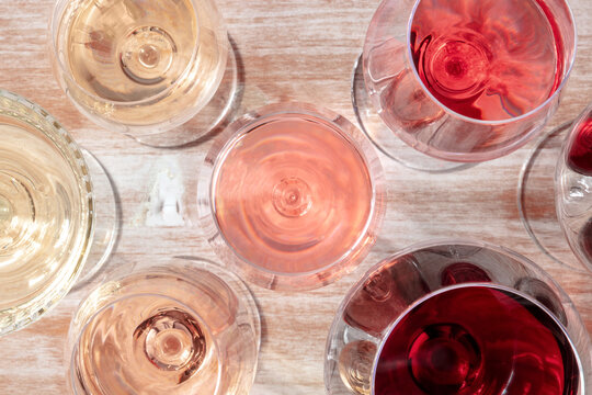 Various glasses of wine, overhead flat lay shot on a wooden background