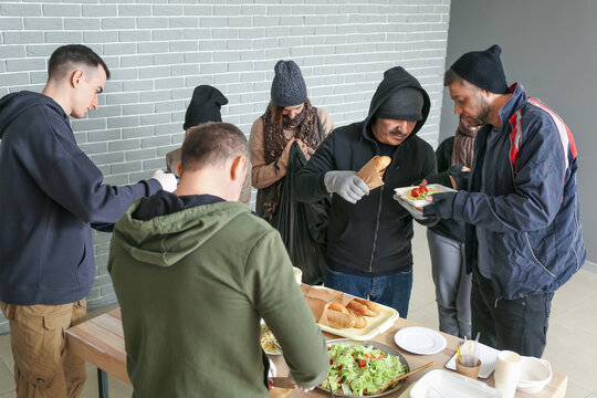 Volunteers giving food to homeless people in warming center