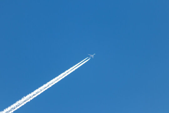 Flying airplane on a journey through the blue sky with a long white smoking exhaust plume and jetwash shows international transportation and globalization transatlantic holidays with pilots