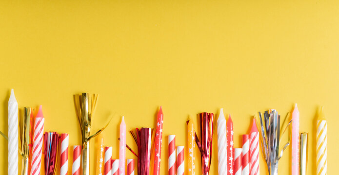 yellow birthday flatlay. colored paper tubes with wax candles. holiday concept, greeting card. copyspace