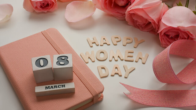 8 March Happy Women's day on white table decorated with pink flowers, ribbon and notebook