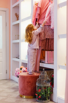 Little baby girl in pyjamas standing on an Ottoman and chooses clothes in a closet on the high rack.