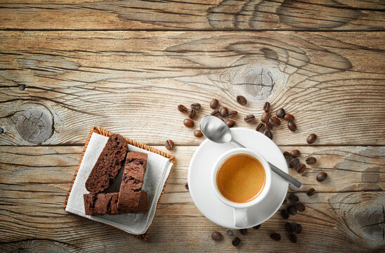 Espresso cup, biscuits and coffee beans on wooden background, top view, space for text.