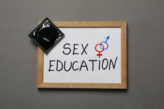 Chalkboard with text Sex Education and condom on gray background