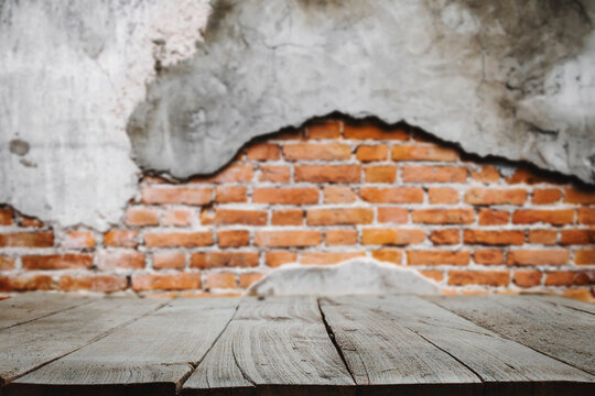 Empty dark wooden table in front  background of Old red brick wall texture.
