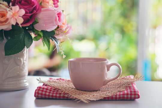 Coffee Break Time. A cup of coffee, and Rose Flower vase place on white home office.