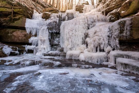 Naturschauspiel im Winter, zu Eis erstarrter Wasserfall in einer Waldschlucht.