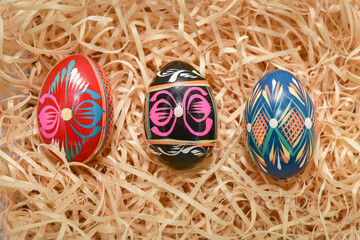three painted for easter multi-colored chicken eggs lie on beige sawdust