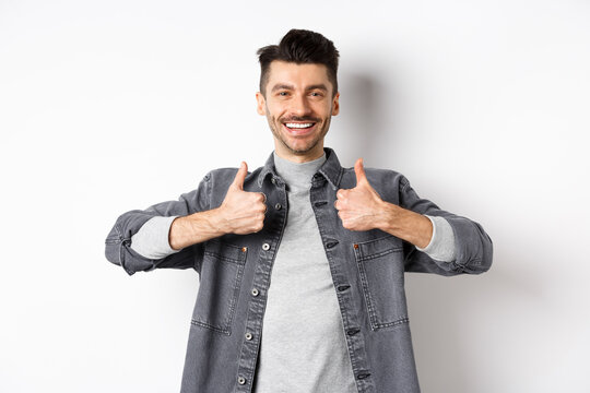 Handsome smiling man showing thumbs-up in approval, praise good work, satisfied with nice choice, recommending something cool, standing on white background