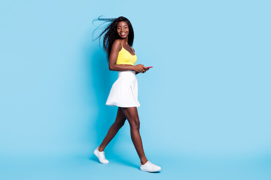 Photo of adorable dark skin wavy lady wear yellow tank-top holding modern gadget walking isolated blue color background