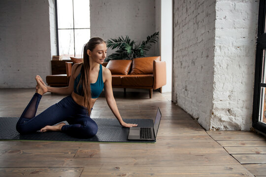 Young sporty woman practicing yoga and stretching body at home using laptop for online class or virtual tutorials.