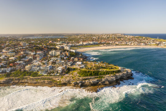 Aerial view of Tamarama townscape with Nelson Bay and Bronte beach in foreground, a surfing beach with open pool, New South Wales, Australia.