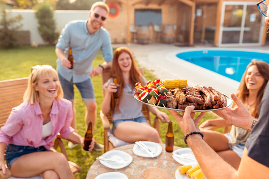 Friends having poolside backyard barbecue party