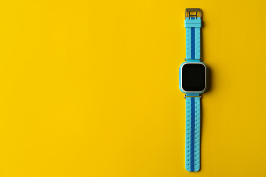 Kid smart watch on yellow background, top view. Space for text