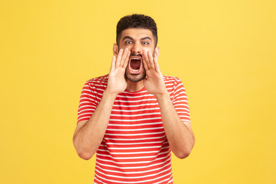 Angry nervous bearded man in striped t-shirt loudly yelling widely opening mouth holding hands on face, screaming announcing his opinion. Indoor studio shot isolated on yellow background