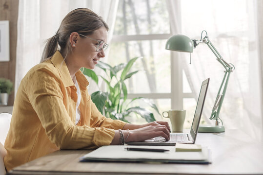 Young businesswoman sitting at desk and working from home