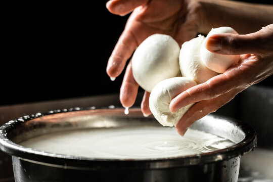 A woman working in a small family creamery is processing the final steps of making a cheese. Italian hard cheese silano or caciocavallo, mozzarella