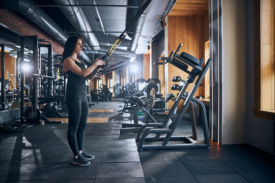 Sportyn young woman during suspension training indoors