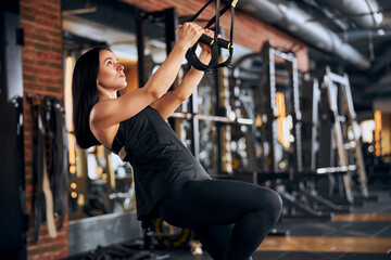 Determined young woman during suspension workout indoors