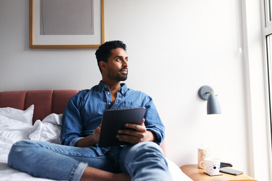 Man Lying On Bed Working From Home On Digital Tablet