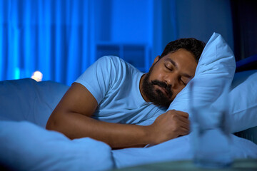 Fototapeta people, bedtime and rest concept - indian man sleeping in bed at home at night obraz