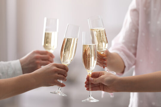 People clinking glasses of champagne against blurred background, closeup