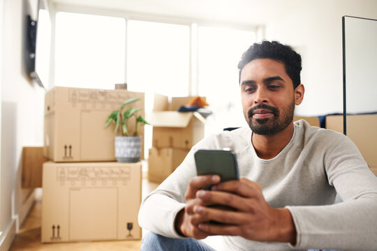 Young Man With Mobile Phone In Lounge Of New Home On Moving Day Surrounded By Removal Boxes
