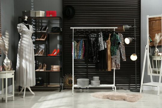 Rack with collection of beautiful festive clothes in stylish room interior
