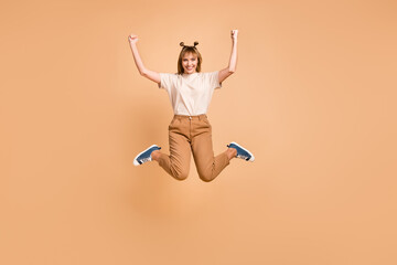 Wall Mural - Full length photo of girl jump raise fists wear t-shirt trousers footwear isolated beige color background