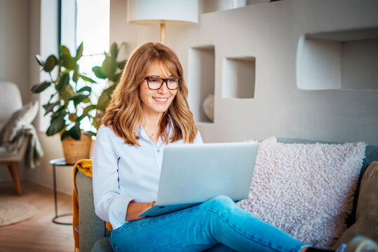 Middle aged woman using laptop while working from home