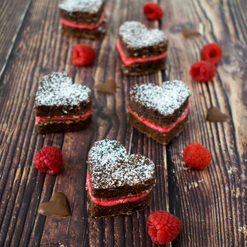 Heart-shaped brownie cookies with fresh raspberry cream.