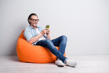 Full body photo of cheerful man happy smile seat bean bag chat type browse cellphone isolated over...
