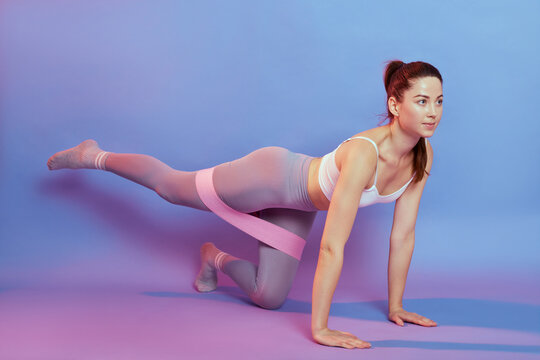 Young beautiful girl with ponytail, has pleasant appearance, looking straight ahead, dresses gray leggins and white top, lady posing on all fours, using resistance band for training butt.