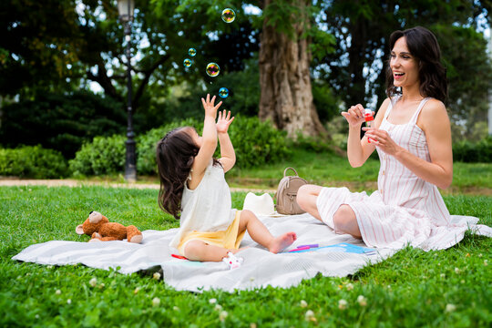 Joyful mommy and daughter playing with bubbles in park