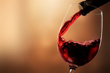 Obraz Red wine pouring from the bottle in glass - fototapety do salonu