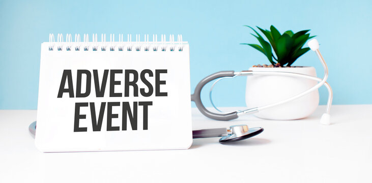 The text ADVERSE EVENT is written on notepad near a stethoscope on a blue background. Medical concept