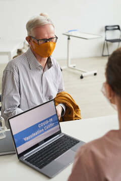 Vertical portrait of white haired senior man wearing mask while registering for covid vaccine at medical center, copy space
