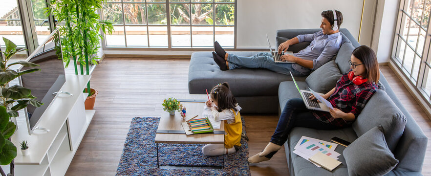 Multiracial family, father, mother, and little daughter stay together at home. Mom and dad working with laptop notebook computer while young girl does homework. Work from home and new normal concept