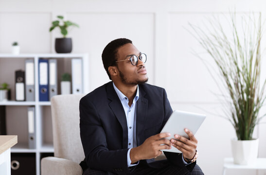 Pensive african american young businessman using digital tablet in office