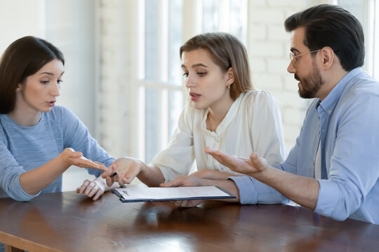 Confused young couple dissatisfied with contract terms of conditions, unhappy clients feeling disappointed discussing agreement details with real estate agent, broke or financial expert at meeting.