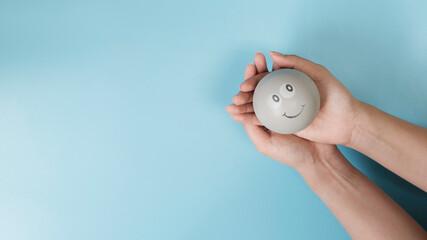 Fototapeta Hand holding smile ball, metaphor positive thinking