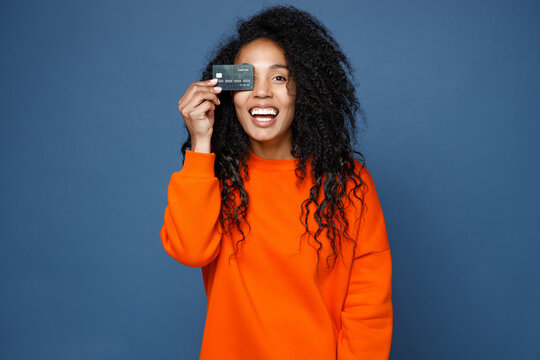 Cheerful laughing young african american woman in casual basic bright orange sweatshirt standing covering eye with credit bank card looking camera isolated on blue color background studio portrait.