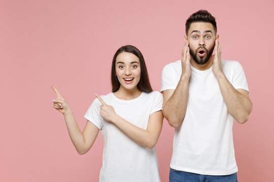 Young cheerful couple two friends man woman in white basic blank print design t-shirt pointing aside on workspace commercial area copy space mock up isolated on pastel pink background studio portrait