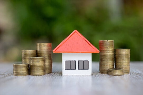 The orange house was placed in the middle between the piles of coins. Home plan ideas, saving money, investing in real estate for saving or investing for a house and paying taxes.
